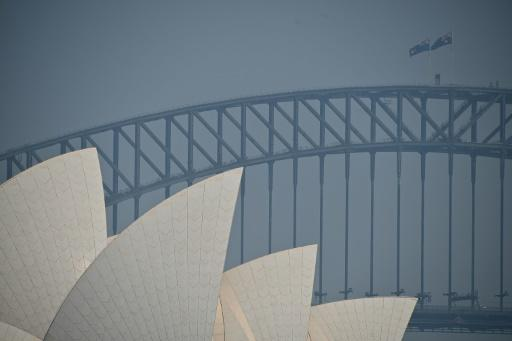 The Sydney Opera House and Harbour Bridge are seen through a smokey haze which blankets Sydney