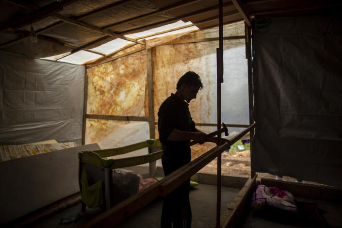 Syrian refugee Raed Mattar, 24, works on his tent, at an informal refugee camp, in the town of Rihaniyye in the northern city of Tripoli, Lebanon, Thursday, April 8, 2021. For many Syrian refugee families in Lebanon, Ramadan comes as a hard life of displacement has gotten even harder after a pandemic year that deepened economic woes in their host country. (AP Photo/Hassan Ammar)