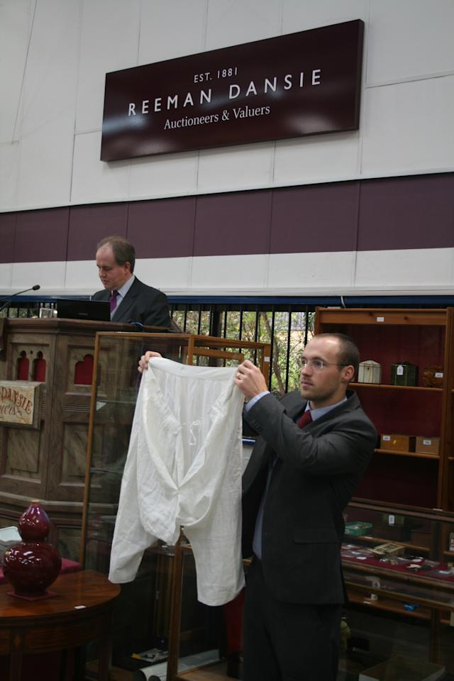 """An auctioneer holds up a pair of linen drawers that belonged to Queen Victoria, with a blue embroidered cipher and a 38"""" waist.  The bloomers were won by a collector in Essex (Reeman Dansie)"""