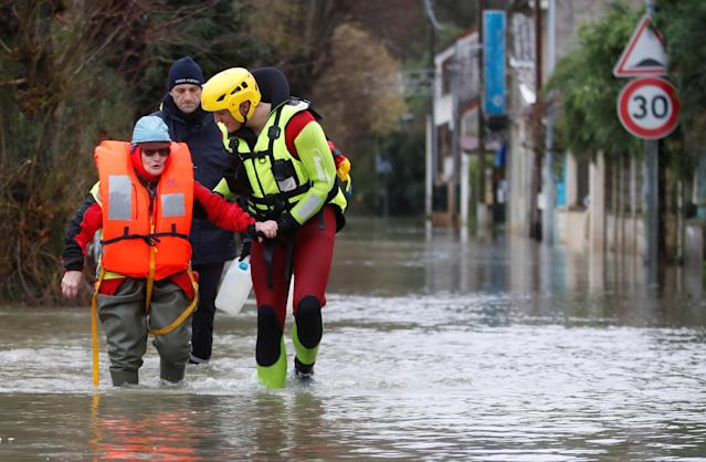 <p>An elderly woman is helped by fire brigade divers after she went back home to feed animals in a flooded residential area in Conde-Sainte-Libiaire, near Paris, France, Jan. 25, 2018. (Photo: Christian Hartmann/Reuters) </p>