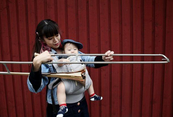 PHOTO: Haruka Kikuchi holds a sliding trombone and her 9-month-old son Shouta. (Radif Anil)