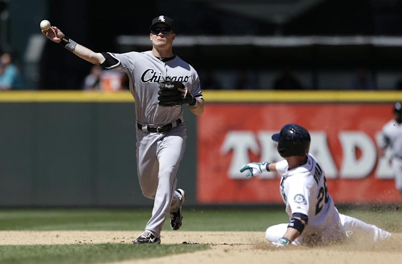Chicago White Sox second baseman Gordon Beckham, left, throws to first after forcing out Seattle Mariners' Brendan Ryan, right, at second base in the seventh inning of a baseball game on Wednesday, June 5, 2013, in Seattle. Beckham completed the throw to first for the double play. (AP Photo/Elaine Thompson)