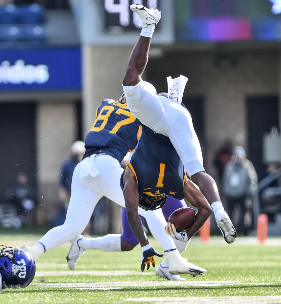 West Virginia wide receiver T.J. Simmons (1) is tackled by TCU safety Ar'Darius Washington (24) during the first half of an NCAA college football game on Saturday, Nov. 14, 2020, in Morgantown, W.Va. (William Wotring/The Dominion-Post via AP)