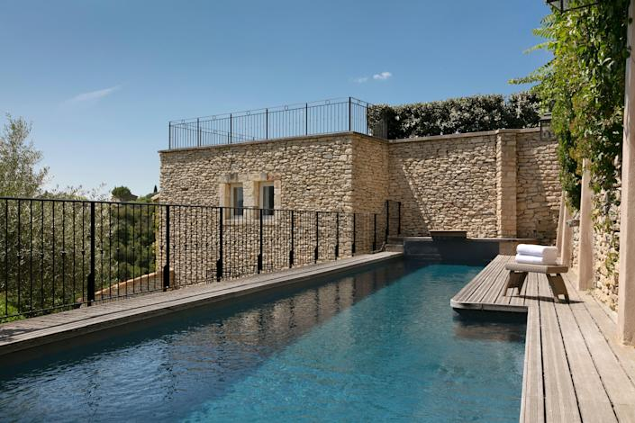 A swimming pool in Airelles Gordes at La Bastide with a view of olive groves and cypresses.