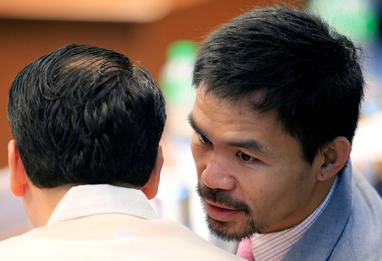 Senator Manny Pacquiao and boxing champion whispers to his colleague Alan Peter Cayetano during a hearing on drug-related extrajudicial killings at Senate headquarters in Pasay city, Metro Manila, Philippines, September 22, 2016. REUTERS/Romeo Ranoco