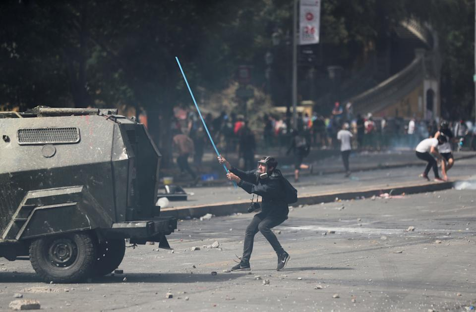 A demonstrator holds a stick to hit an armored vehicle during a protest against Chile's state economic model in Santiago, Chile on Oct. 23, 2019. (Photo: Ivan Alvarado/Reuters)