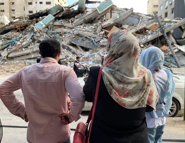 In the hours and days after the ceasefire reached last week, many Gaza residents finally ventured out to survey the damage. In this photo, a family stands in front of what is left of the building that housed the offices of The Associated Press and Al Jazeera.