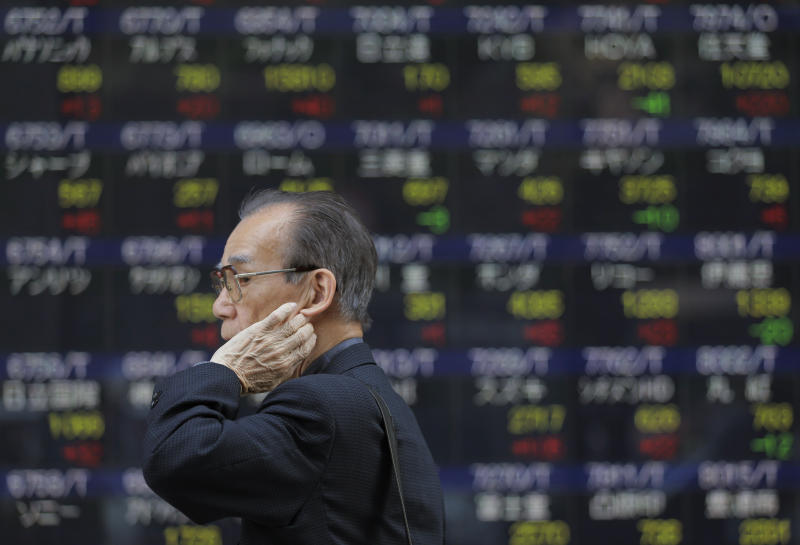 A man walks by an electronic stock board of a securities firm in Tokyo, Friday, May 24, 2013. Asian stocks continued to retreat Friday after being routed the day before by unexpectedly weak Chinese manufacturing and fears the Federal Reserve will start withdrawing its monetary stimulus. Japan's Nikkei 225 index, which plummeted more than 7 percent Thursday, reversed a big morning gain and shed 0.7 percent to 14,391.74 as the yen strengthened against the dollar. (AP Photo/Itsuo Inouye)