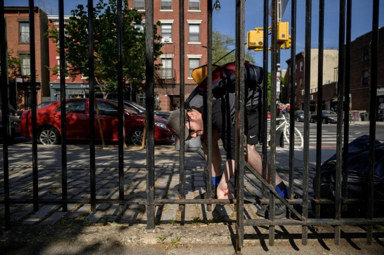 Filmmaker Zack Obid searches for a mini artwork by artist Steve Wasterval hidden in Greenpoint, New York on May 25, 2021