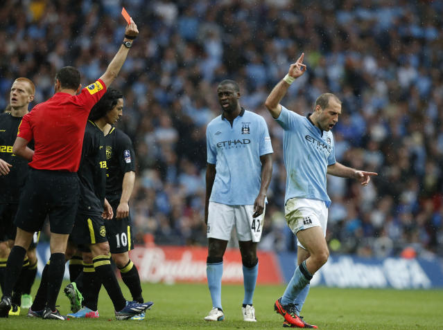 Manchester City's Pablo Zabaleta, right, reacts as he is being shown a red card by referee Andre Marriner after a foul on Wigan Athletic's Callum McManaman during their English FA Cup final soccer match at Wembley Stadium, London, Saturday, May 11, 2013. (AP Photo/Matt Dunham)