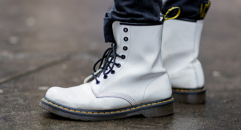 Man wearing white doc martens boots with tucked in pants.