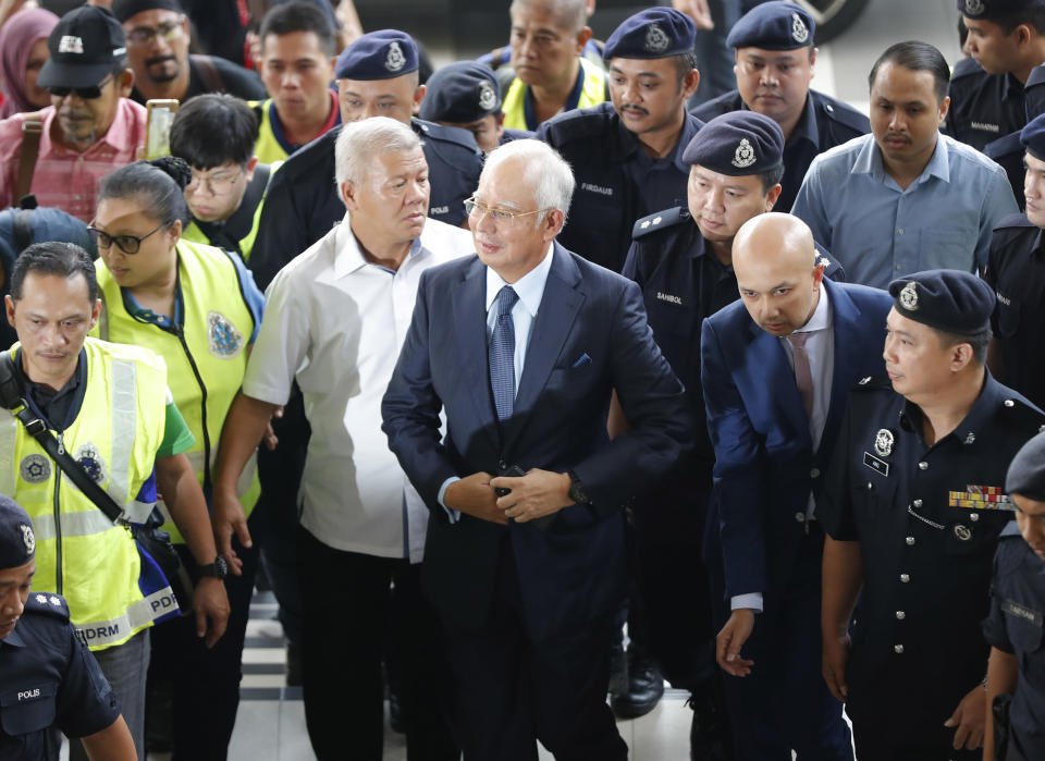 Former Malaysian Prime Minister Najib Razak, center, arrives at Kuala Lumpur High Court in Kuala Lumpur, Malaysia, on Oct. 4, 2018. Najib was found guilty Tuesday, July 28, 2020 in his first corruption trial linked to one of the world's biggest financial scandals - the billion-dollar looting of the 1MDB state investment fund. (AP Photo/Vincent Thian)