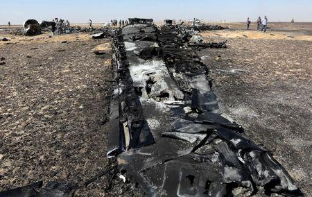 Military investigators from Egypt and Russia stand near the debris of a Russian airliner at the site of its crash at the Hassana area in Arish city, north Egypt