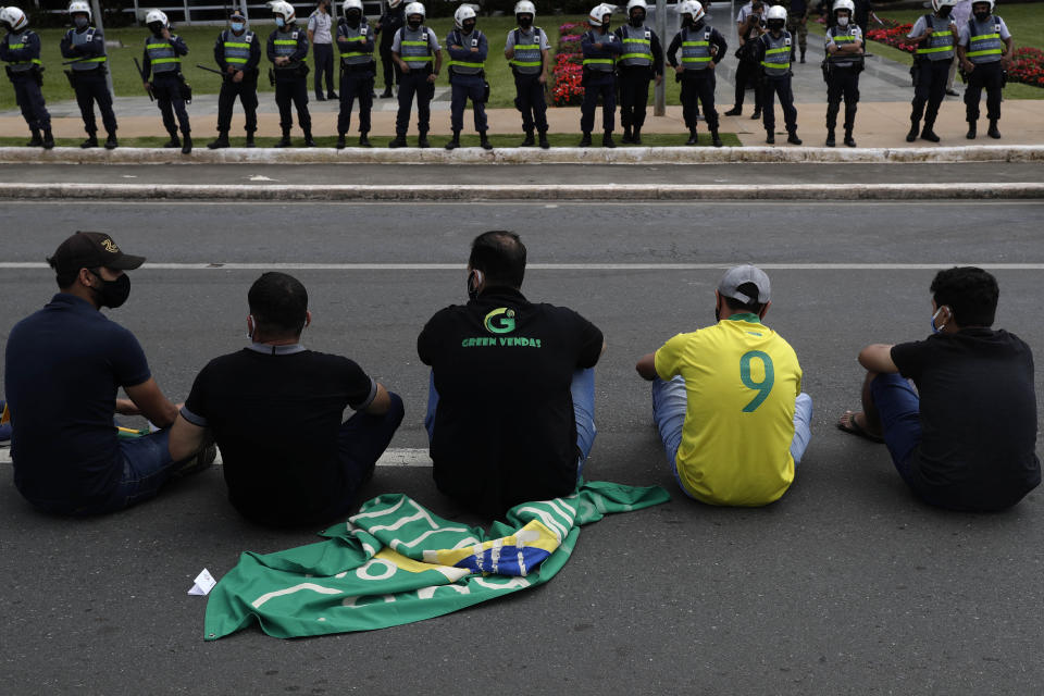 Demonstrators sit in front of police guarding a city government office where they protest a two-week-long lockdown to curb the spread of COVID-19 in Brasilia, Brazil, Monday, March 1, 2021. It's the second lockdown in Brasilia since the start of the pandemic one year ago. (AP Photo/Eraldo Peres)