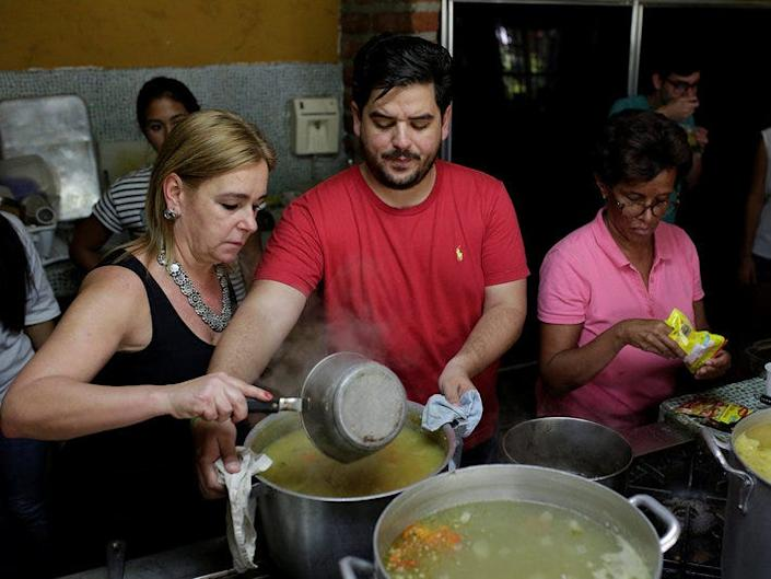 Diego Prada (C), Maria Luisa Pombo (L) and other volunteers of the Make The Difference (Haz La Diferencia) charity initiative prepare soup to be donated, at Maria Luisa's kitchen in Caracas, Venezuela March12, 2017. Picture taken March 12, 2017. REUTERS/Marco Bello