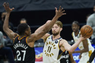 Indiana Pacers' Domantas Sabonis (11) passes around Cleveland Cavaliers' Mfiondu Kabengele (27) in the second half of an NBA basketball game, Monday, May 10, 2021, in Cleveland. (AP Photo/Tony Dejak)