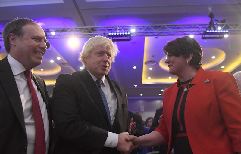 Democratic Unionist Party (DUP) leader Arlene Foster shakes hands with Conservative MP Boris Johnson as Deputy Leader Nigel Dodds looks on, at the DUP annual party conference in Belfast, Northern Ireland November 24, 2018. REUTERS/Clodagh Kilcoyne