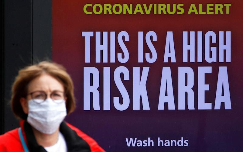 A woman wearing a protective mask walks past a warning sign in Manchester - PHIL NOBLE/REUTERS