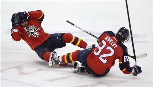 Florida Panthers' John Madden, left, falls after a collision with teammate Tomas Kopecky (82) during the first period of Game 7 in a first-round NHL Stanley Cup playoff hockey series against the New Jersey Devils, in Sunrise, Fla., Wednesday, April 26, 2012. (AP Photo/J Pat Carter)