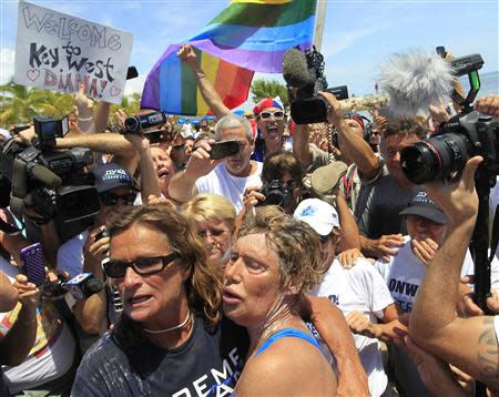 U.S. long-distance swimmer Diana Nyad (front R), 64, is welcomed ashore after completing her swim from Cuba as she arrives in Key West, Florida, September 2, 2013. REUTERS/Andrew Innerarity