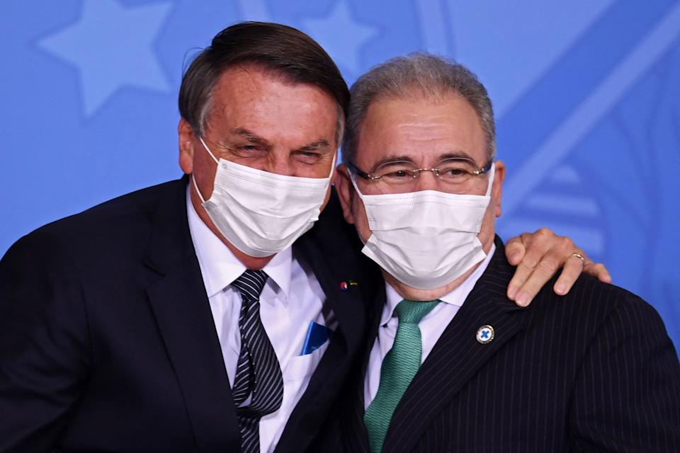 Brazilian President Jair Bolsonaro (L) embraces his Health Minister Marcelo Queiroga during the announcement that the public healthcare system will cover expanded heel prick tests at Planalto Palace, in Brasilia, on May 26, 2021. (Photo by EVARISTO SA / AFP) (Photo by EVARISTO SA/AFP via Getty Images)
