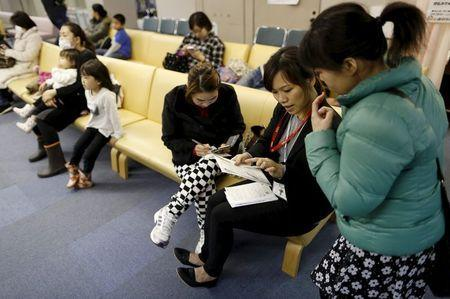 Dang Nguyen Thuc Vien (2nd R), a 32-year-old daughter of refugees from south Vietnam, helps a local Vietnamese resident in Japan as an interpreter at a hospital in Kanagawa prefecture, south of Tokyo, Japan, November 25, 2015. REUTERS/Yuya Shino