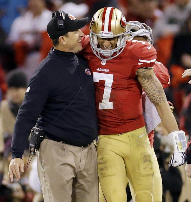 FILE - In this Jan. 12, 2013 file photo, San Francisco 49ers head coach Jim Harbaugh celebrats with quarterback Colin Kaepernick (7) after Kaepernick's 56-yard touchdown run against the Green Bay Packers during the third quarter of an NFC divisional playoff NFL football game in San Francisco. The 49ers are scheduled to play the Seattle Seahawks on Sunday, Sept. 15, 2013. (AP Photo/Ben Margot, file)