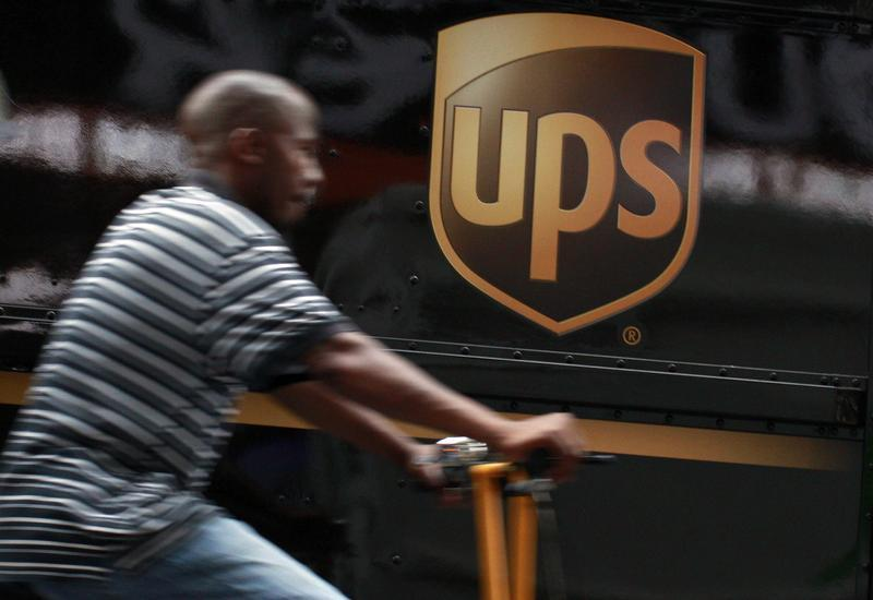 A bicycle delivery man rides past a UPS truck in New York's Times Square