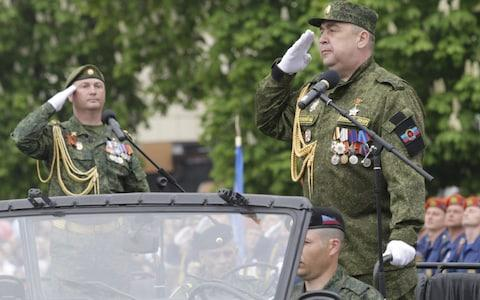 Igor Plotnitsky, head of the self-proclaimed Lugansk People's Republic, salutes during Victory Day military parade. - Credit: Alexander Ermochenko/Reuters