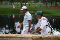 Hideki Matsuyama, of Japan, walks on the 15th hole with his caddie Shota Hayafuji during the third round of the Masters golf tournament on Saturday, April 10, 2021, in Augusta, Ga. (AP Photo/Matt Slocum)