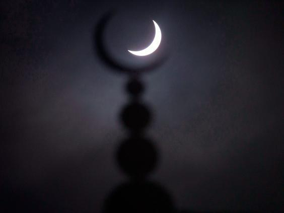 A partial solar eclipse in seen above a mosque in Oxford, central England