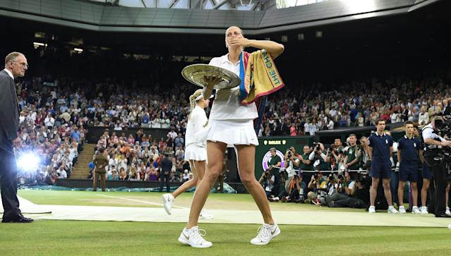 Petra Kvitova of Czech Republic blows a kiss to the crowd as she holds the trophy after winning the women's singles final against Eugenie Bouchard of Canada the All England Lawn Tennis Championships at Wimbledon, London, Saturday, July, 5, 2014. (AP Photo/Andy Rain, Pool)