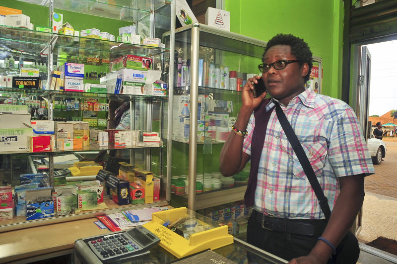 Prominent gay rights activist and Sexual Minorities Uganda program coordinator Pepe Julian Onziema makes a phone call while in a pharmacy in the suburbs of Kampala, Uganda Wednesday, Feb. 26, 2014. Uganda's health minister said Wednesday that gays will not be discriminated against by medical workers after the country's president signed a law that strengthens criminal penalties against homosexuals, but prominent gay rights activist Pepe Julian Onziema said that well-known homosexuals face constant discrimination and abuse and recalled being ignored many times by medical workers who served others as they gossiped about his sexual orientation. (AP Photo/Stephen Wandera)