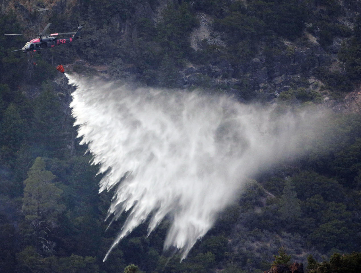 Fire crews drop water unto the Ponderosa Fire from a helicopter near Mineral, Calif., Thursday, Aug. 23, 2012. The Ponderosa Fire was 57 percent contained, with full containment expected early next week. The blaze threatened 900 other homes Thursday as it burned a new front to the south. More than 2,500 firefighters are battling the wildfire, which grew to 44 square miles in the hills about 25 miles southeast of Redding. (AP Photo/Marcio Jose Sanchez)