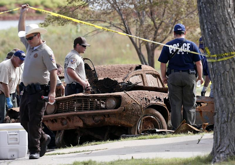 Law enforcement officials from multiple agencies examine the two cars pulled from Foss Lake, in Foss, Okla., Wednesday, Sept. 18, 2013. The Oklahoma State Medical Examiner's Office says authorities have recovered skeletal remains of multiple bodies in the Oklahoma lake where the cars were recovered. (AP Photo/Sue Ogrocki)