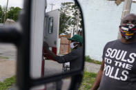 A man is reflected in a side mirror of a mobile help unit as he receives medical supplies during a harm reduction effort in the city in St. Louis on Friday, May 21, 2021. (AP Photo/Brynn Anderson)