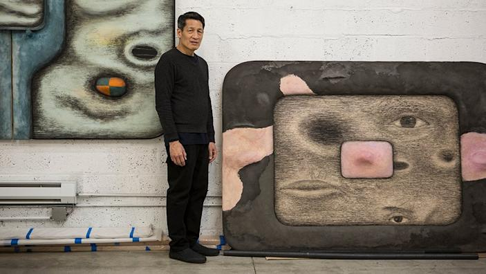 Artist Tishan Hsu stands in front of his technology-infused artworks.