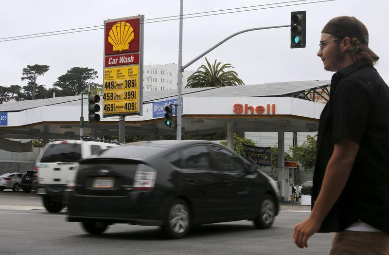 A pedestrian stands near a sign displaying the cost of gasoline at a filling station in San Francisco