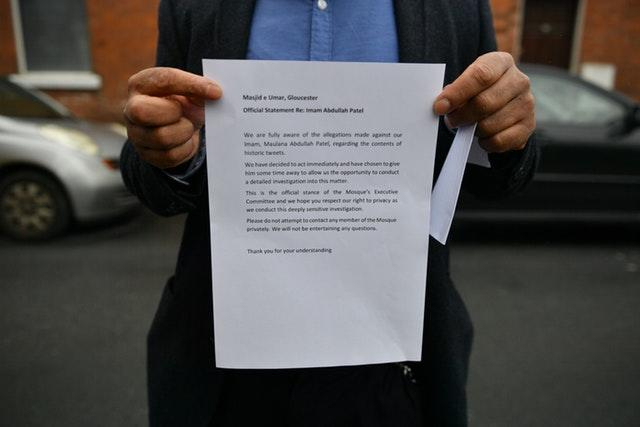 A member of the Masjid e Umar mosque in Gloucester, where Abdullah Patel is imam holds a statement outside the mosque (Ben Birchall/PA)