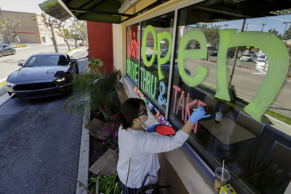 FILE - In this March 26, 2020, file photo, Lucy Kwak paints a sign on the window of a fast food chain's restaurant indicating that the drive-thru window is still open as well as a takeout option during the coronavirus outbreak in Garden Grove, Calif. Taxpayers will pay restaurants to make three meals a day for California's millions of seniors during the coronavirus pandemic, Gov. Gavin Newsom announced Friday, April 24, 2020, putting the industry back to work and generating sales tax collections for cash-strapped local governments. California has about 5.7 million people 65 and older, but not all of them will be eligible, and some will have to meet income thresholds. (AP Photo/Chris Carlson, File)