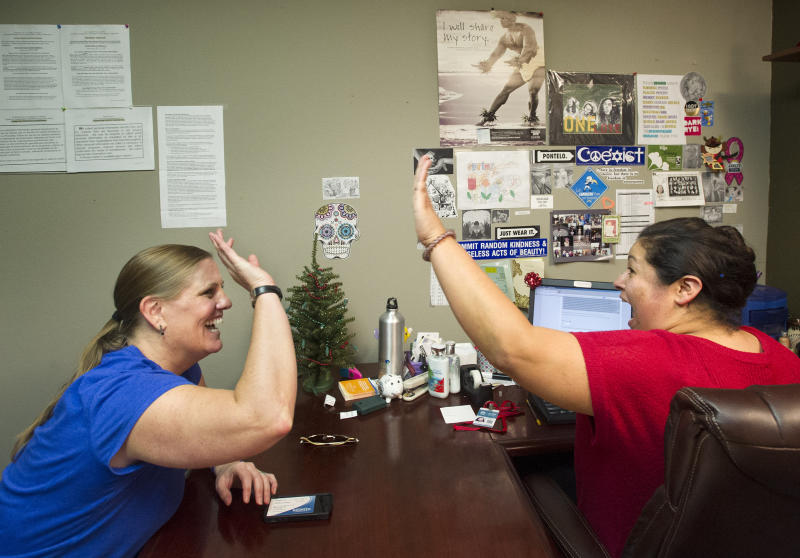 Lisa Donlea, 41, of Irvine, left, and Susan Roberts, a certified enrollment officer, celebrate after working on Donlea's federal health insurance exchange enrollment online for one hour and 47 minutes at the Irvine AIDS Services Foundation where Roberts is a housing case manager, Monday, Dec. 23, 2013, in Laguna Beach, Calif. It was expected to take about 20 minutes, but the high-demand site where consumers sign up was excruciatingly slow. (AP Photo/The Orange County Register, Cindy Yamanaka)