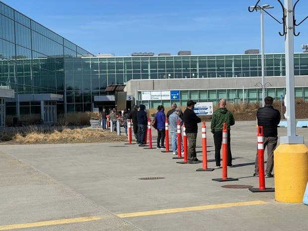 People line up outside the Edmonton Expo Centre's COVID-19 vaccination site Tuesday as Alberta allows those 40 and over to get the AstraZeneca vaccine for the first time.  (Travis McEwan/CBC - image credit)