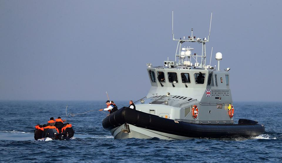 A Border Force vessel assist a group of people thought to be migrants on board from their inflatable dinghy in the Channel (Photo: ASSOCIATED PRESS)
