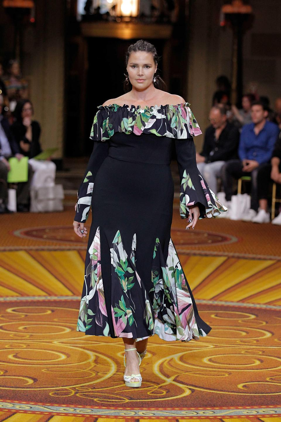 <p>Candice Huffine has become a popular mainstay at New York Fashion Week, seen here walking for Christian Siriano's show wearing an off-the-shoulder dress. (Photo: Getty Images) </p>