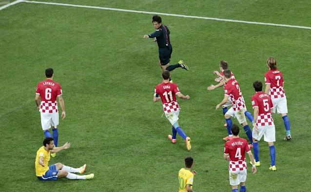 Referee Yuichi Nishimura from Japan, top, decides on foul against Brazil's Fred, bottom left, during the group A World Cup soccer match between Brazil and Croatia, the opening game of the tournament, in the Itaquerao Stadium in Sao Paulo, Brazil, Thursday, June 12, 2014. (AP Photo/Shuji Kajiyama)