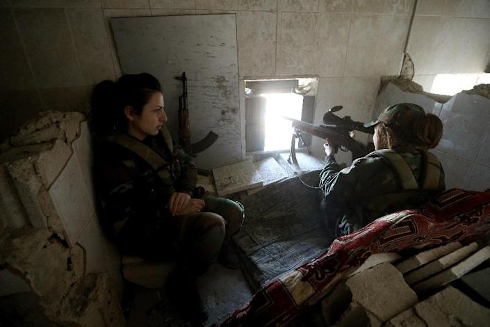 A female Syrian sniper from the Republican Guard commando battalion aims fire during clashes with rebels in the restive Jobar area, in eastern Damascus, on March 25, 2015 (AFP Photo/Joseph Eid)