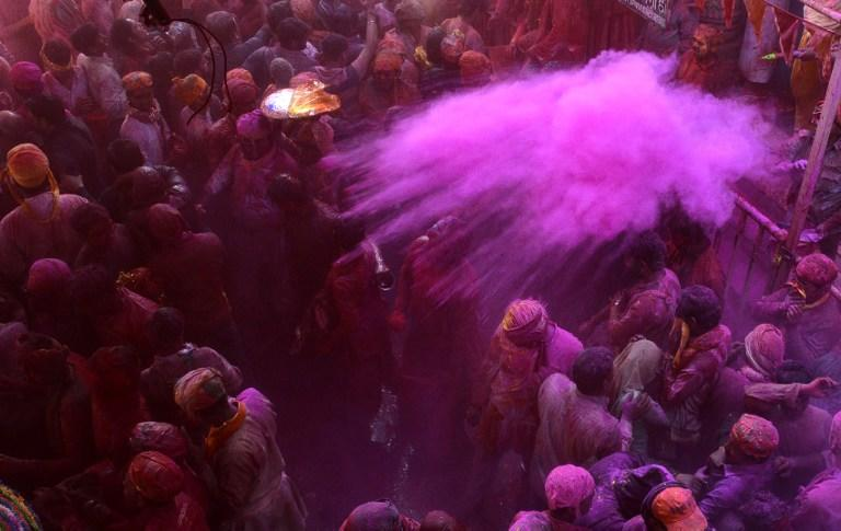 """<p>Indian devotees throw coloured powder during celebrations for Lathmar Holi in Barsana on the outskirts of Mathura in the northern Indian state of Uttar Pradesh.<br />Lathmar Holi is a local celebration of the Hindu festival of Holi, usually some days ahead of the actual festival – it translates as 'that Holi in which people hit with sticks"""". / AFP PHOTO / STR </p>"""