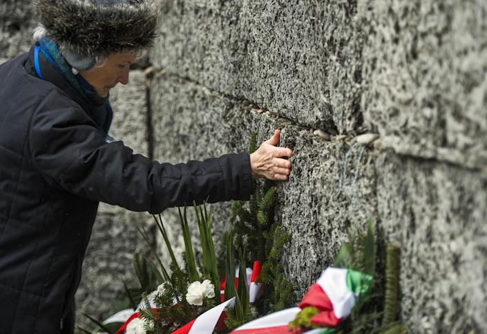 """A Holocaust survivor pays tribute to fallen comrades, putting her hand on the """"death wall"""" execution spot in the former Auschwitz concentration camp in Oswiecim, Poland, on January 27, 2015 (AFP Photo/Odd Andersen)"""