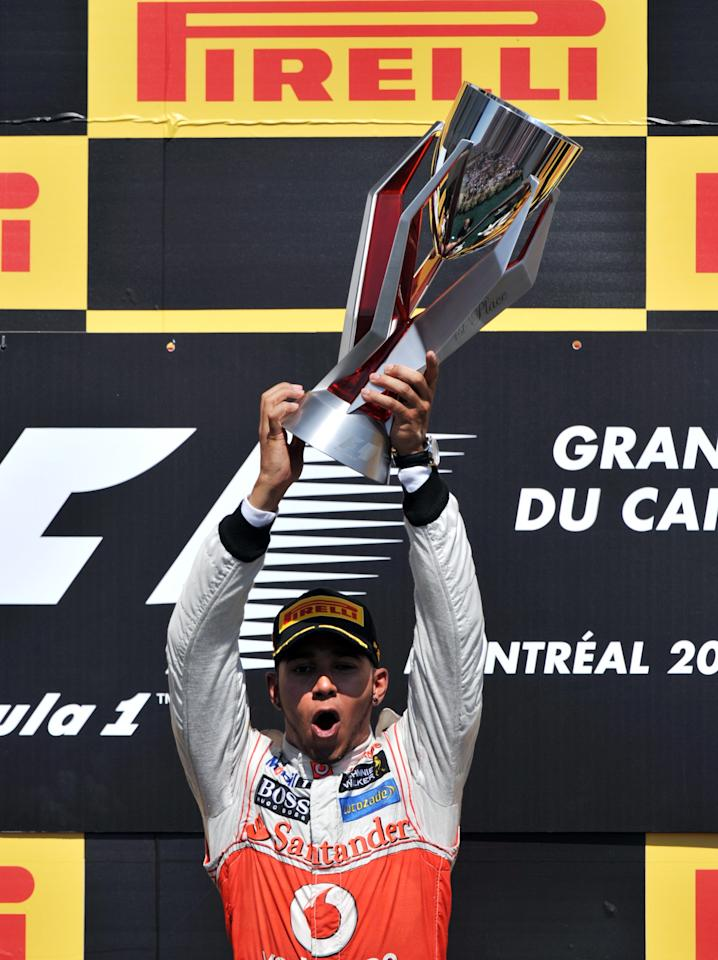 McLaren Mercedes driver Lewis Hamilton of Britain holds up the trophy after winning the Canadian Formula One Grand Prix on June 10, 2012 at the Circuit Gilles Villeneuve in Montreal.     AFP PHOTO/Stan HONDASTAN HONDA/AFP/GettyImages