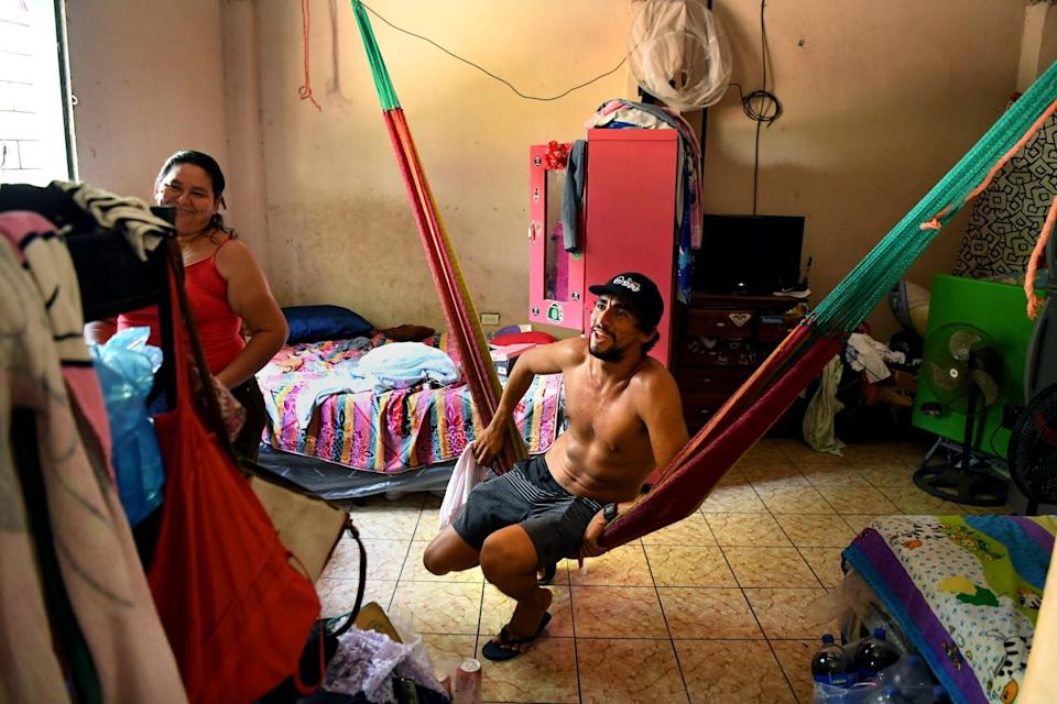 Surfer Bryan Perez sits in the room where he grew up with his mother Maria Perez